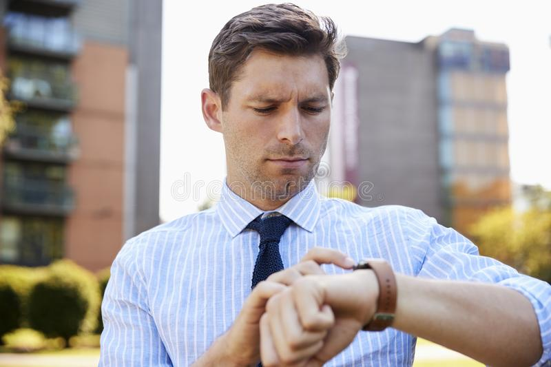 Businessman Walking Through City Park Looking At Smart Watch stock photos