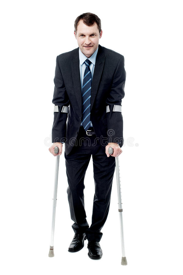 Businessman walking with crutches. Handsome businessman with crutches trying to walk royalty free stock photography