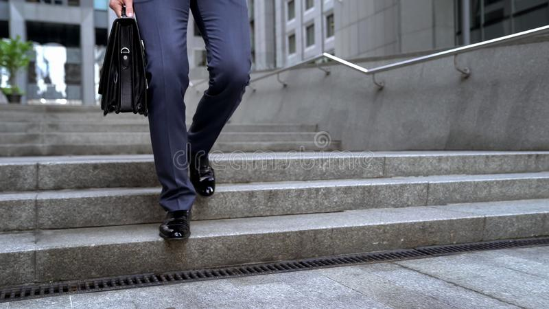 Businessman walking downstairs holding briefcase, going to important meeting stock photography