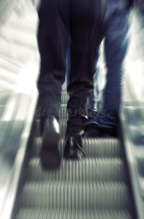 Businessman walking on escalator royalty free stock photos