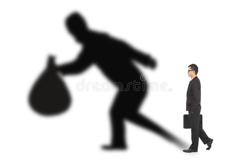 Businessman walking and holding bag with thief shadow stock photos