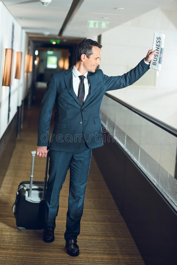 businessman walking down hotel corridor with a suitcase and waving stock image