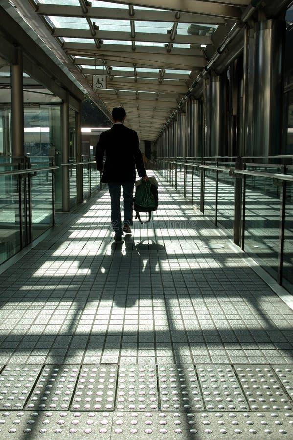 Businessman walking on modern bridge royalty free stock photography
