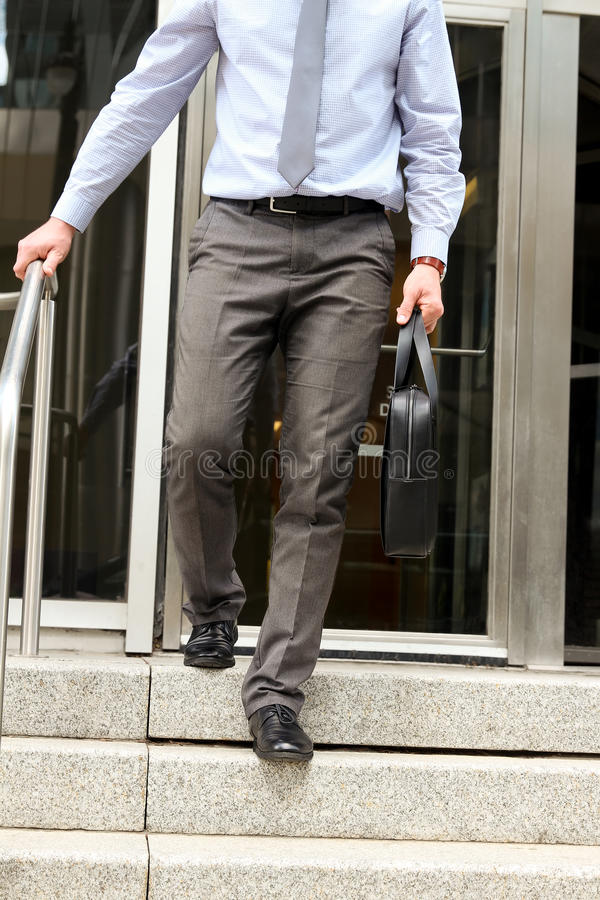 Businessman walking out from the office after working day and holding a leather briefcase in his hand stock photography