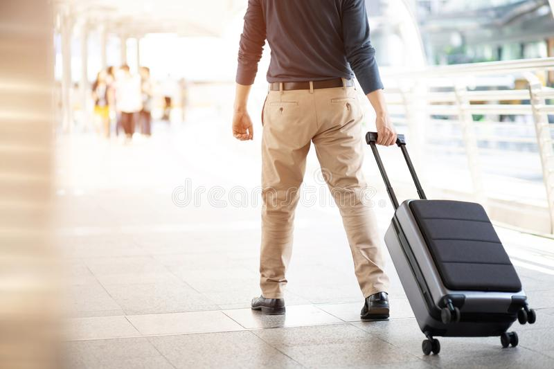 Businessman walking outside public transport building with luggage in rush hour. Business traveler pulling suitcase in modern airp. Ort terminal. baggage stock photography