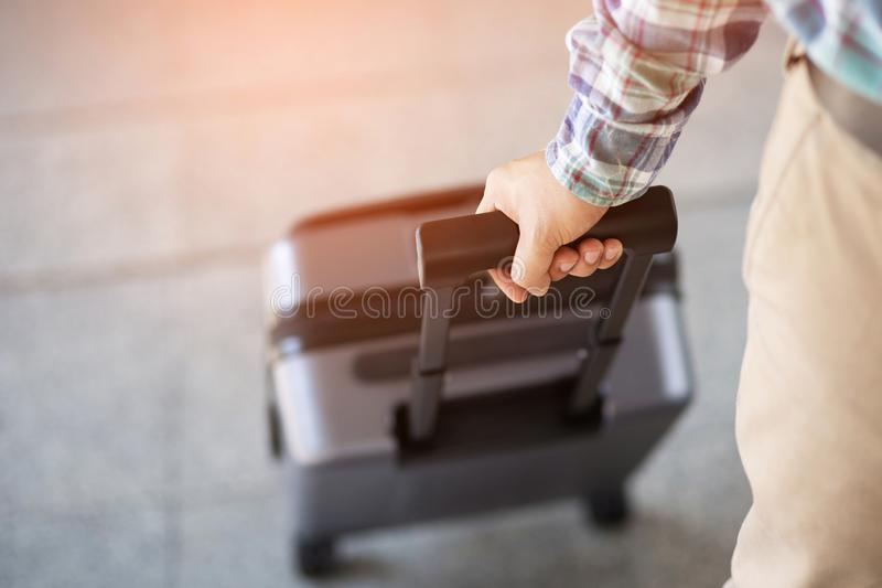 Businessman walking outside public transport building with luggage in rush hour. Business traveler pulling suitcase in modern airp. Ort terminal. baggage royalty free stock photography