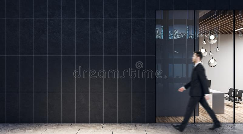 Businessman walking past dark wall business center with modern light conference room royalty free stock photos