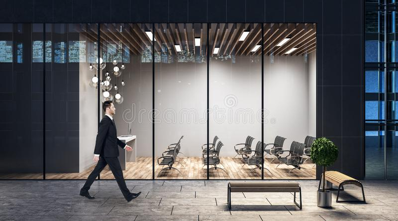 Businessman walking past evening business center with spacious conference room royalty free stock photos