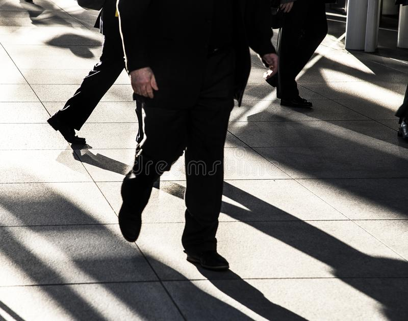 Businessman walking quickly on city sidewalk wearing black suit silhouetted in the sun with long dark shadows and bright light stock images