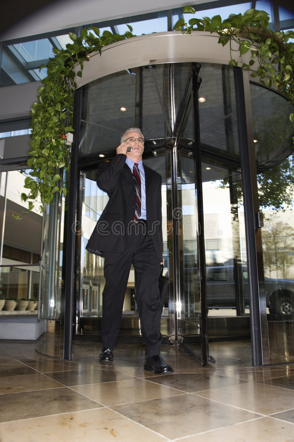 Businessman Walking Through Revolving Door. Royalty Free Stock Images