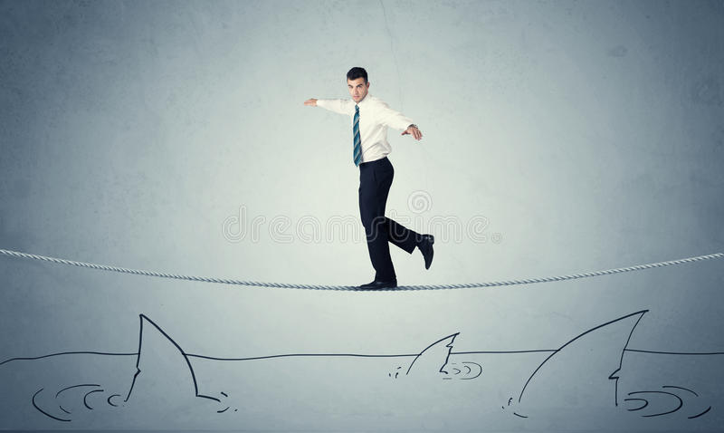 Businessman walking on rope above sharks royalty free stock photo