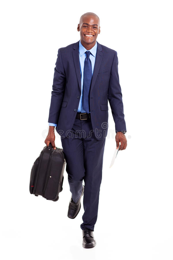 Businessman walking suitcase. African businessman walking with suitcase isolated on white stock photography