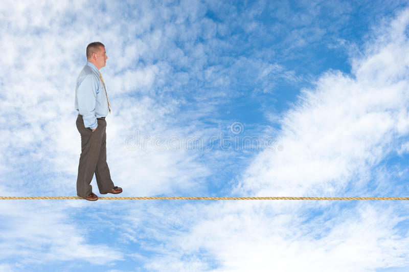 Businessman walking on tightrope. A businessman walks across a tightrope contemplating success, risk, vision and the way forward royalty free stock photography