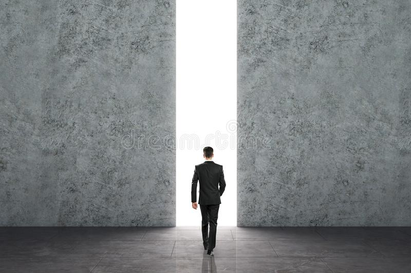 Opportunity and success concept. Businessman walking towards bright opening in concrete wall. Opportunity and success concept stock photography