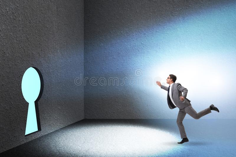 The businessman walking towards keyhole in challenge concept stock image