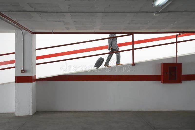 Download Businessman Walking Up Ramp With Luggage In Parking Garage Stock Photo - Image: 33891738