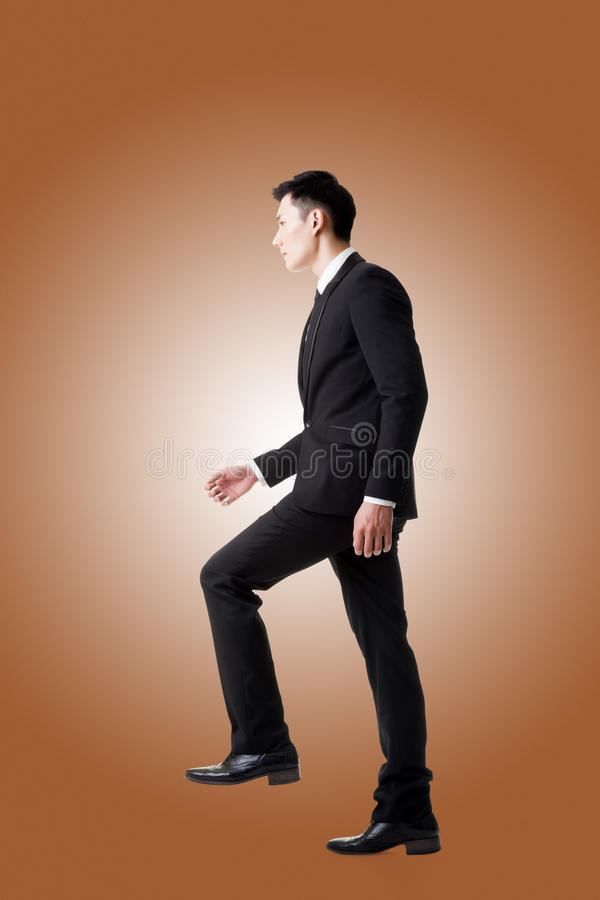 Businessman walking up on stairs stock photo
