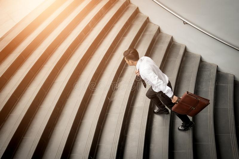 Businessman walking up on stairs and holding briefcase royalty free stock images