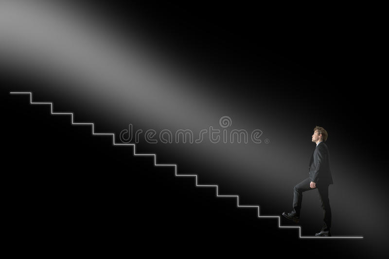 Businessman walking upwards towards the light on conceptual stairway over black background royalty free stock photos