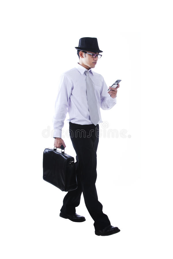 Businessman Walking While Using Mobile Phone Stock Photo