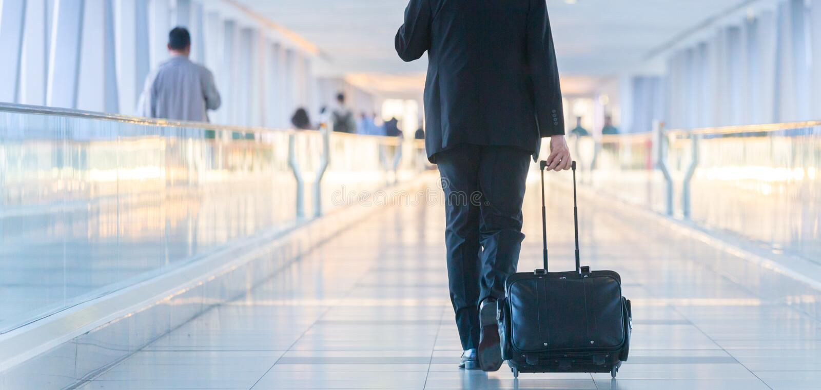 Businessman walking and wheeling a trolley suitcase at the lobby, talking on a mobile phone. Business travel concept. royalty free stock photography