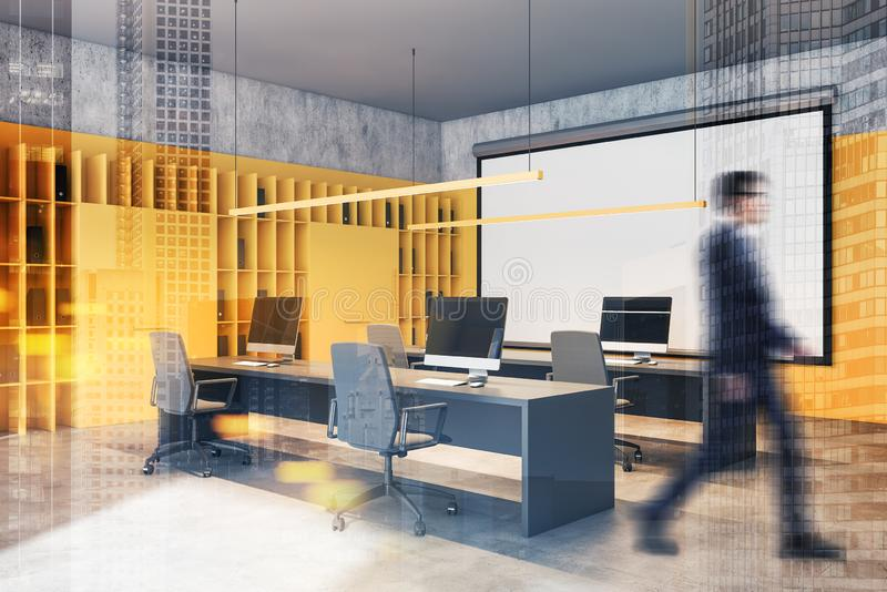 Businessman walking in yellow office with screen. Blurry businessman walking in modern open space office with white and yellow walls, rows of computer desks and royalty free stock photos