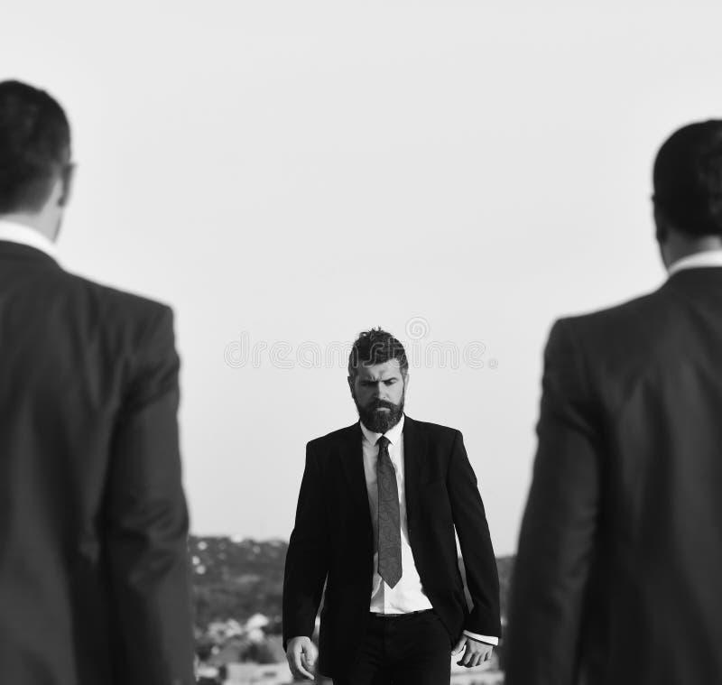 Businessman walks towards two men, defocused. Man with beard and serious face walks forward, close up. stock image