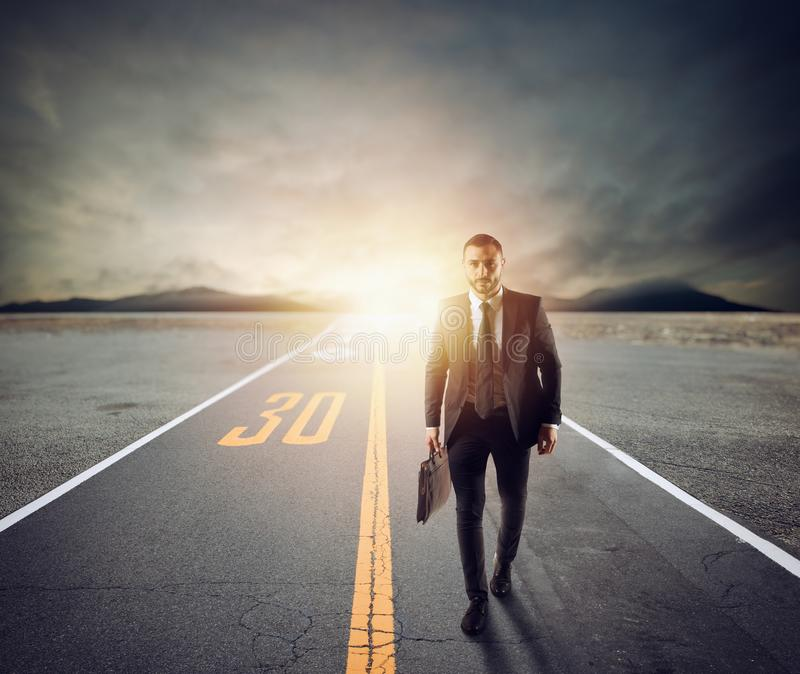 Businessman walks on an unknown road for a new adventure. Concept of determination stock images