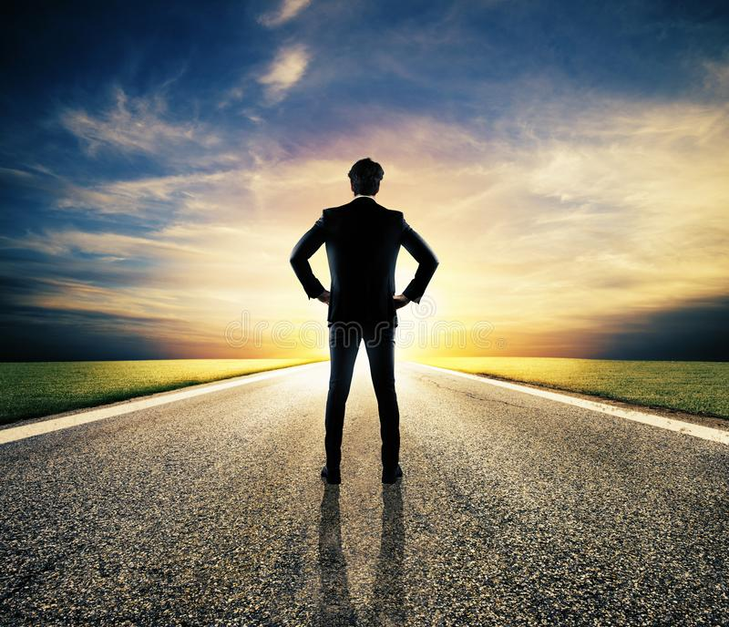 Businessman walks on an unknown road for a new adventure stock photos