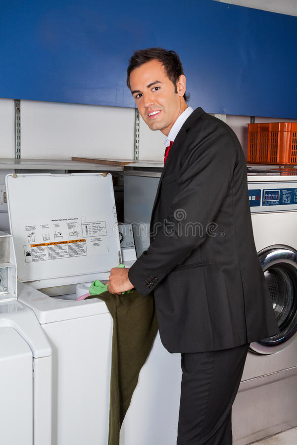 Businessman Washing Clothes At Laundromat royalty free stock image