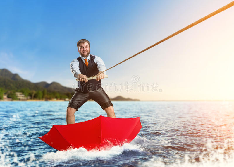 Businessman on water skis in umbrella stock images