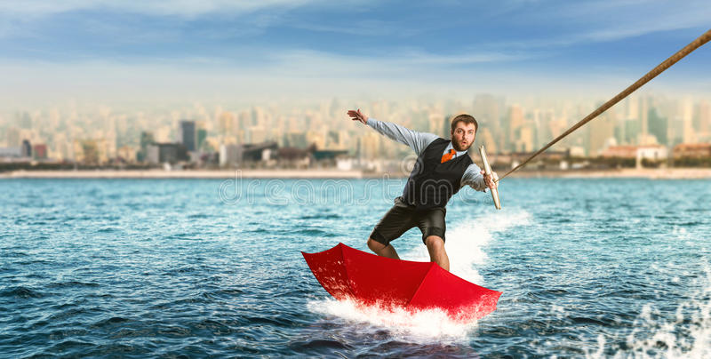 Businessman on water skis in umbrella royalty free stock images