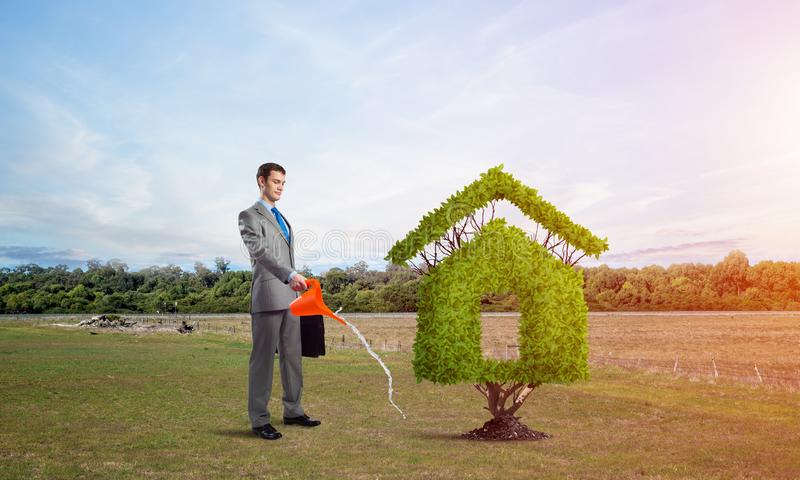 Businessman watering green plant in shape of house. In field. Business growth and development. Nature landscape with dry soil and blue sky. Green and eco stock photos