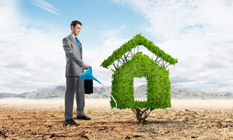 Businessman watering green plant in shape of house. In desert. Green and eco friendly technology. Business development to success. Real estate company growth royalty free stock images