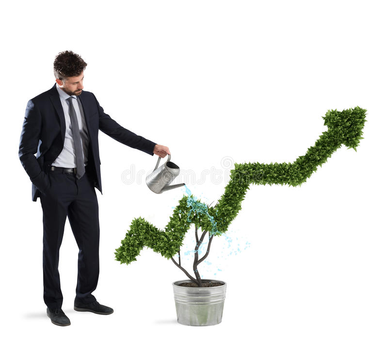 Businessman that watering a plant with a shape of arrow. Concept of growing of company economy . royalty free stock photo