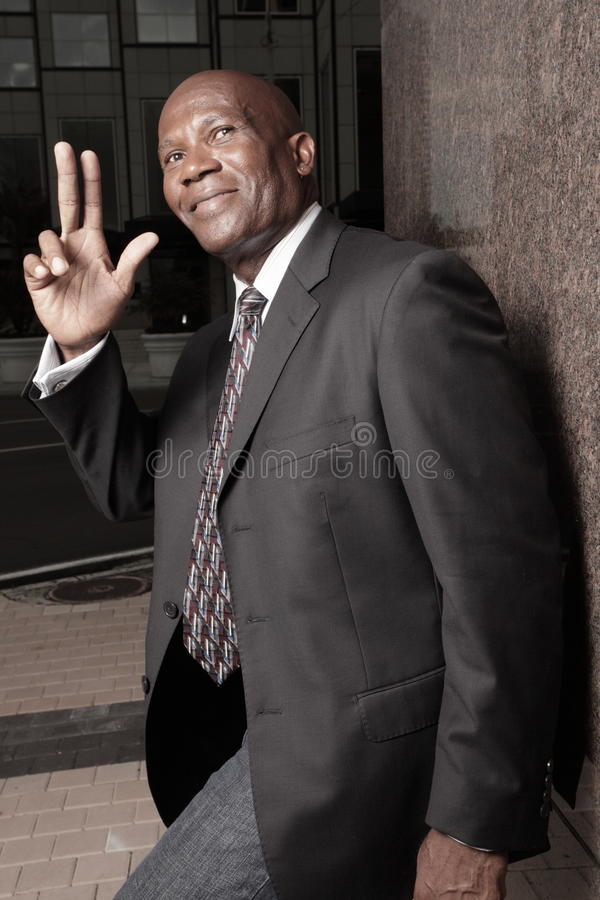 Businessman waving and smiling royalty free stock photo