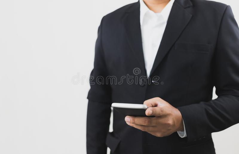 Businessman wear black suit hand holding and touch screen smart phone. Telecommunication and Technology concept. royalty free stock photography