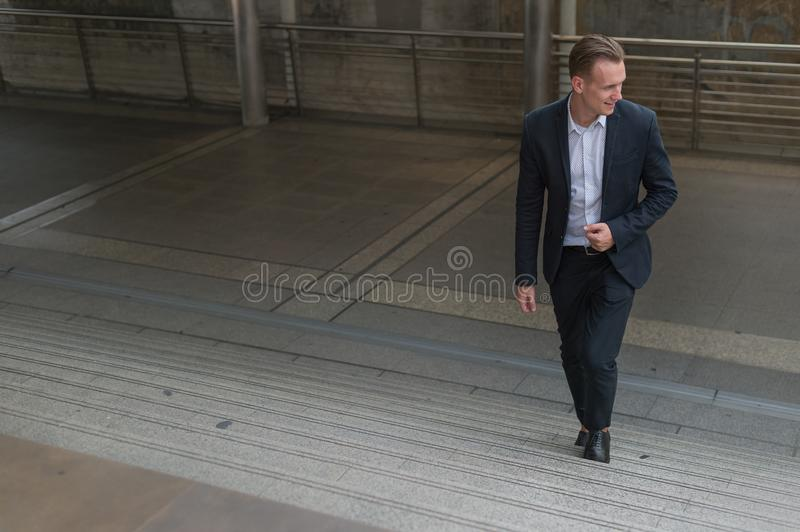 Businessman wear black suit walking stepping up stair in modern city, business grow up and success concept. Ambitions concept royalty free stock photography