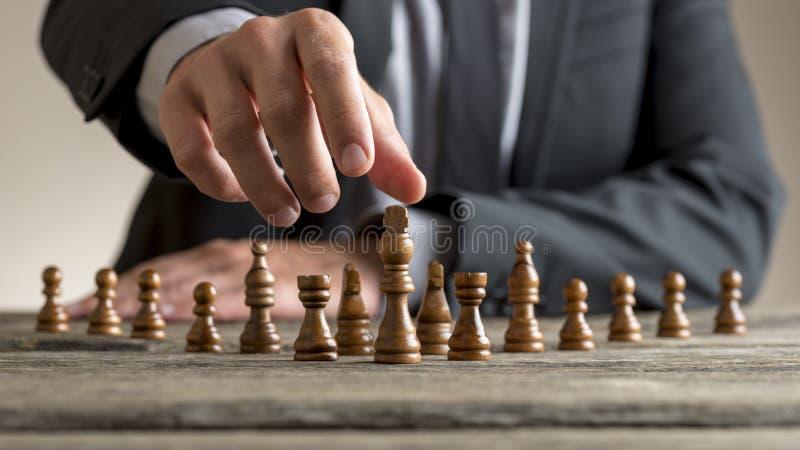 Businessman wearing business suit reaching dark King chess piece stock image