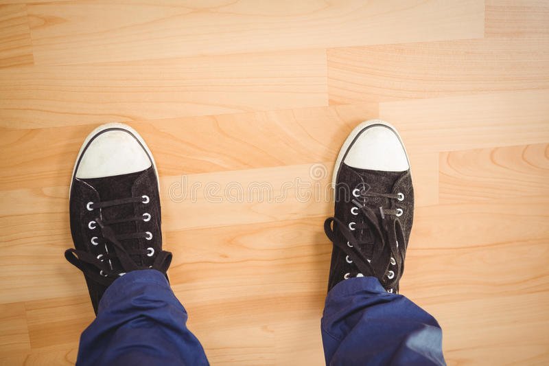 Businessman wearing canvas shoes standing on hardwood floor stock photo