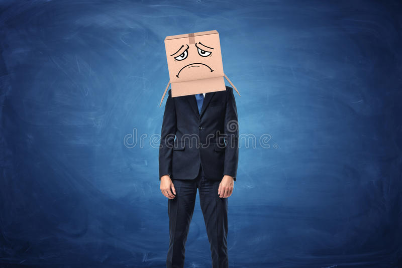Businessman wearing cardboard box with drawn sad face on his head stock images