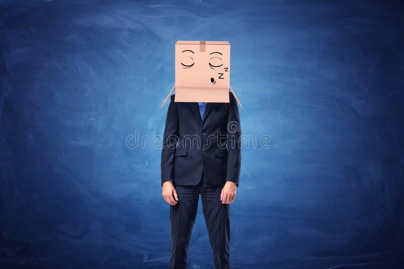 Businessman is wearing cardboard box on head with sleepy face. Businessman is wearing a cardboard box on his head with a sleepy face painted on it on blue royalty free stock image