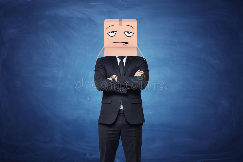 Businessman is wearing cardboard box on his head with painted disappointed face stock image