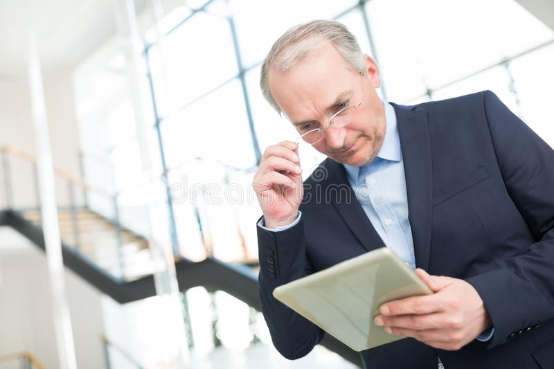 Businessman Wearing Eyeglasses While Reading On Digital Tablet stock images