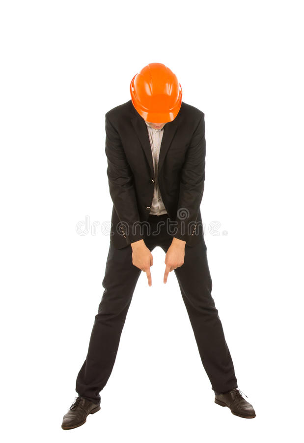 Businessman Wearing Hard Hat Pointing Down. Full Length of Businessman Wearing Orange Hard Hat Pointing and Looking Down in Studio with White Background royalty free stock photography
