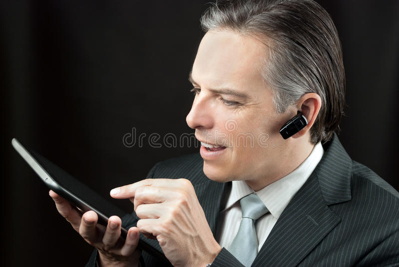 Download Businessman Wearing Headset Using Tablet Royalty Free Stock Image - Image: 27126786
