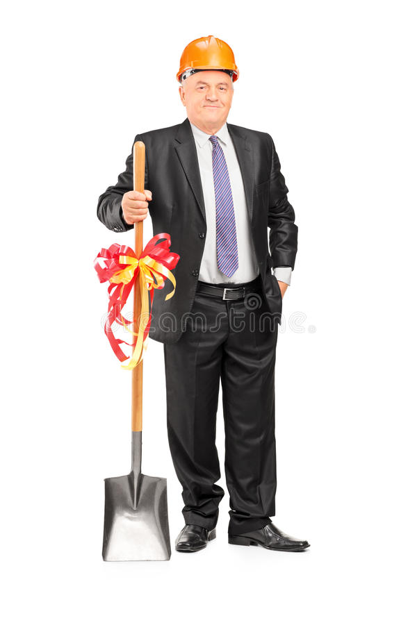 Businessman wearing helmet and holding a shovel with ribbon on i. Full length portrait of a businessman wearing helmet and holding a shovel with ribbon on it on stock photos