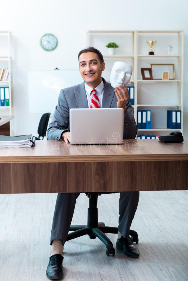 Businessman wearing mask in hypocrisy concept royalty free stock photo
