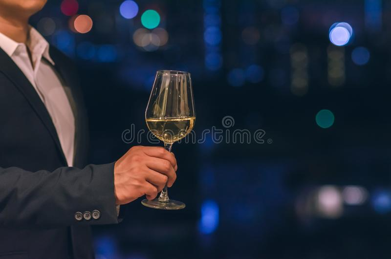Businessman wearing navy blue color suit stands at the rooftop bar toasting a glass of white wine with dark background of city royalty free stock photo