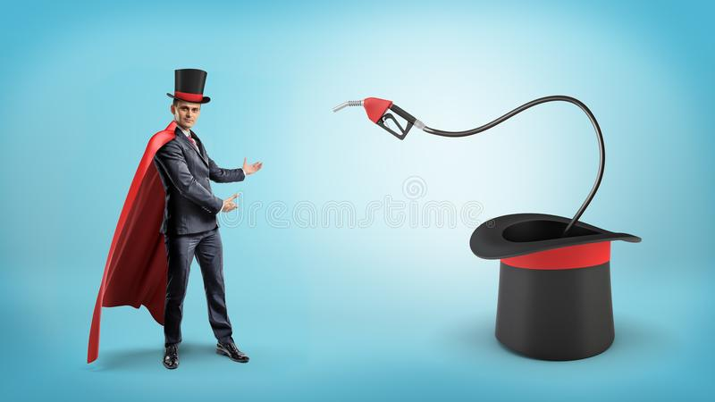 A businessman wearing a red cape and a big illusionist`s hat shows a fuel nozzle inside a large magician`s hat. royalty free stock photos